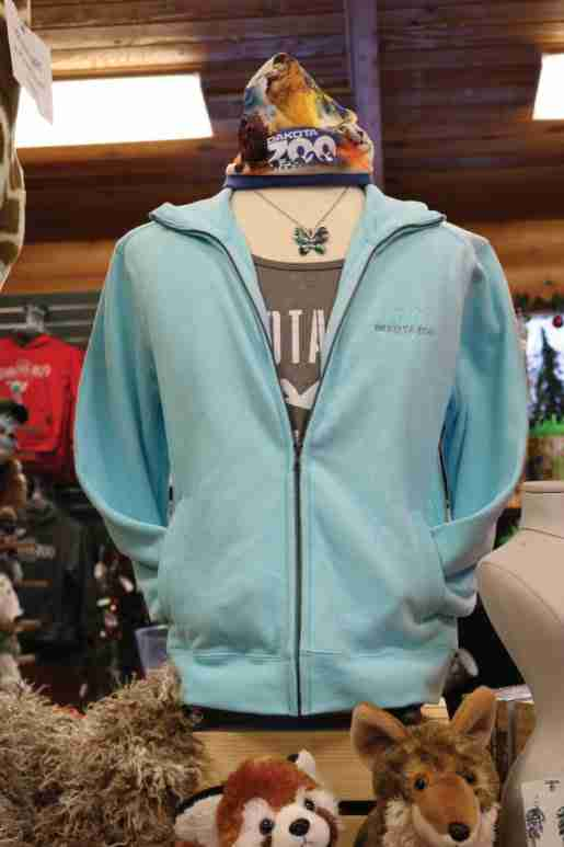 A hoodie in unique aqua is displayed with a necklace, hat and plush at the Dakota Zoo. A store official advised not overstuffing racks with apparel, but instead stocking two pieces of each size.