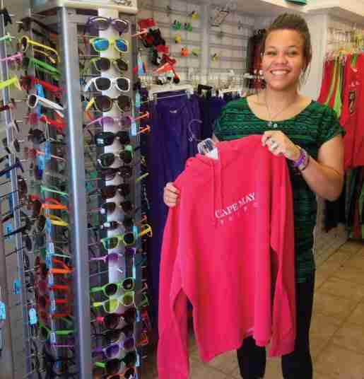 A woman photographed with a sweatshirt and sunglasses at Sunset Beach Gifts in Cape May Point, N.J. Shoppers can be reminded to buy sunglasses by placing them near the fitting room, where glasses can be tried on with apparel, or with a sunscreen display, according to the owner.